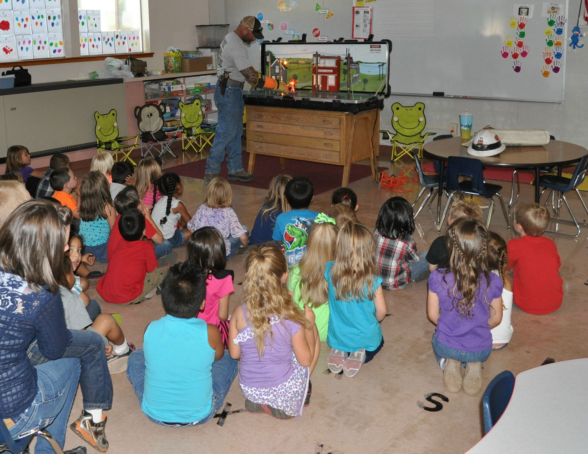 Lineman teaching group of young children about voltage safety